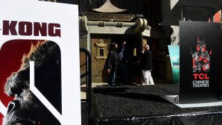 People enter the TCL Chinese Theater in Hollywood, California during its reopening on March 29, 2021. - The four directors of current and previous Godzilla and King Kong movies attended the reopening of the TCL Chinese Theater ahead of the new release of the latest Godzilla v Kong movie which will open on April 1st.
