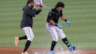 Miami Marlins' Miguel Rojas pours a bucket of water onto Jorge Alfaro after Alfaro hit a double to drive in the winning run in the 10th inning of the team's baseball game against the San Francisco Giants, Saturday, April 17, 2021, in Miami. The Marlins won 7-6.
