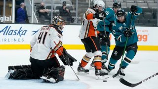Anaheim Ducks goaltender Anthony Stolarz (41) blocks a shot by San Jose Sharks right wing Kevin Labanc (62) as center Adam Henrique (14) defends during the first period of an NHL hockey game Wednesday, April 14, 2021, in San Jose, California.