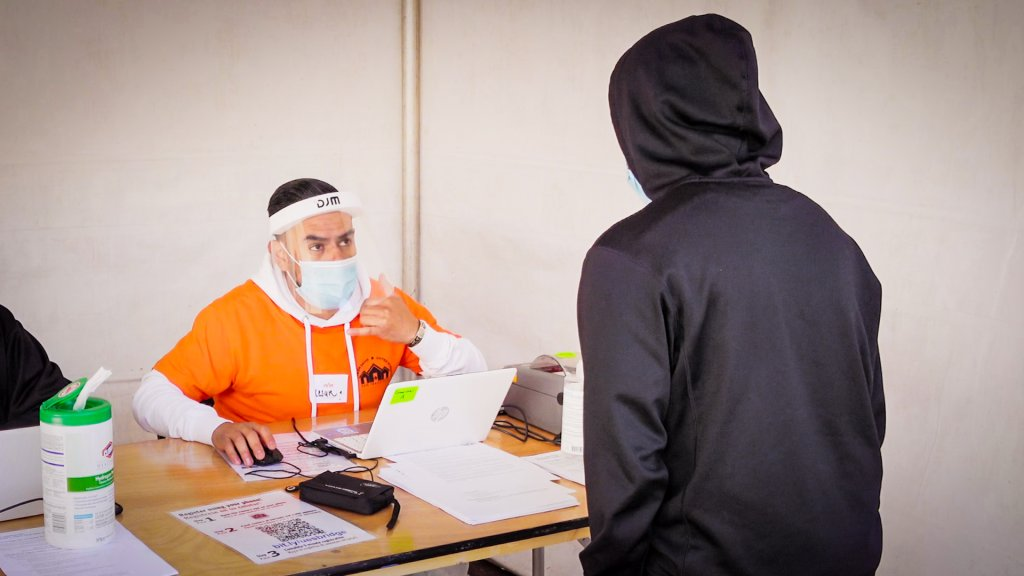 a man in an orange shirt, surgical mask and face shield sits at a desk as a person in a black hoodie approaches