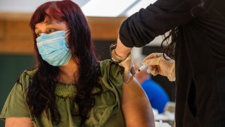 Woman receives COVID-19 vaccine.