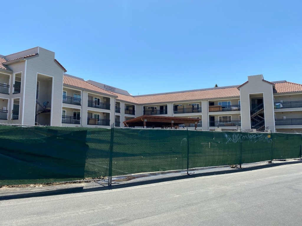 A photo of the Country Inn & Suites by Radisson in Vallejo, surrounded by a fence for construction.