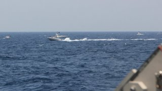 """In this image provided by the U.S. Navy, an Iranian Islamic Revolutionary Guard Corps Navy (IRGCN) fast in-shore attack craft (FIAC), a type of speedboat armed with machine guns, speeds near U.S. naval vessels transiting the Strait of Hormuz, Monday, May 10, 2021. U.S. officials say a group of 13 armed speedboats of Iran's Revolutionary Guard made """"unsafe and unprofessional"""" high-speed maneuvers toward U.S. Navy vessels in the Strait of Hormuz on Monday. A U.S. Coast Guard cutter fired warning shots when two of the Iranian boats came dangerously close."""