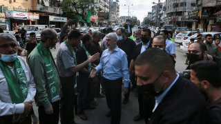 Top Hamas leader in Gaza, Yehiyeh Sinwar, center, pays his respects at a house of mourning for a Hamas commander killed in the war, in Gaza City