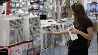 A woman looks at air conditioners for sale in a P.C. Richard & Son store, in New York, Sunday, July 1, 2012.