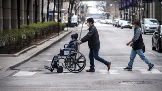 a man pushes a wheelchair towards Northwestern Memorial Hospital in Chicago, Illinois.