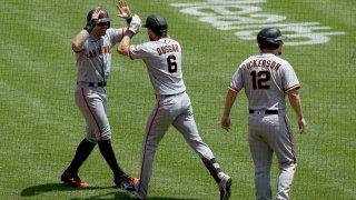 Evan Longoria #10, Steven Duggar #6, and Alex Dickerson #12 of the San Francisco Giants celebrate.