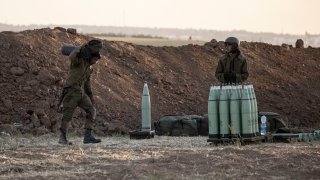 Israeli soldier arms artillery shells next to an artillery unit, at the Israeli Gaza border, Wednesday, May 19, 2021.