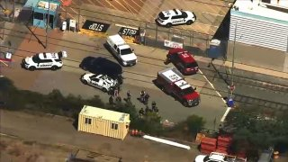 Authorities work at the scene of a mass shooting at a VTA rail yard in San Jose.