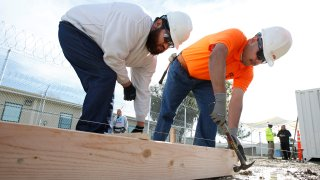Two men construct a frame to hold concrete at one of the vocational classes at the O.H. Close Youth Correctional Facility