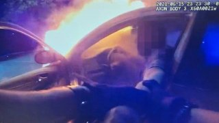 An officer pulls a driver out of a burning vehicle.