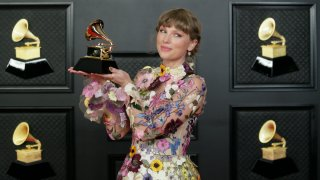 Taylor Swift poses with a Grammy Award