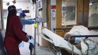 An 81-year-old African American COVID-19 patient is brought from the emergency room into the ICU ward at Roseland Community Hospital on December 14, 2020 in Chicago, Illinois.