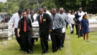 Pall bearers carry the casket of Alton Sterling to his gravesite at the Mount Pilgrim Benevolent Society Cemetery July 15, 2016 in Baton Rouge, Louisiana. Sterling was shot July 5 outside a Baton Rouge convenience store in an encounter with police that was caught on video.