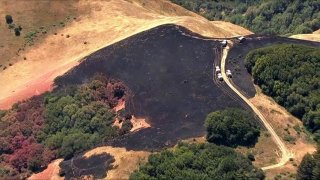 Firefighters work at the scene of a brush fire in Marin County.