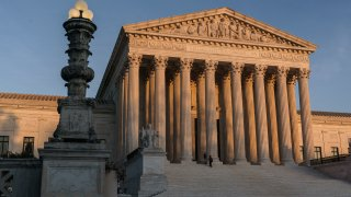 In this Nov. 6, 2020, file photo, the Supreme Court is seen at sundown in Washington. The state of California has agreed to pay more than $2 million in legal fees in a settlement with churches that challenged coronavirus closure orders. Church lawyers who successfully took their appeal to the U.S. Supreme Court said Wednesday, June 2, 2021, that the state agreed not to impose restrictions on houses of worship that are greater than those on retail businesses.
