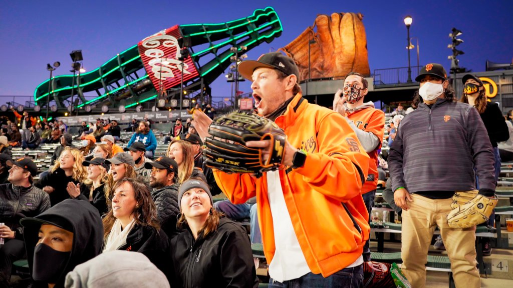 A Giants fan dressed in orange stands up and cheers