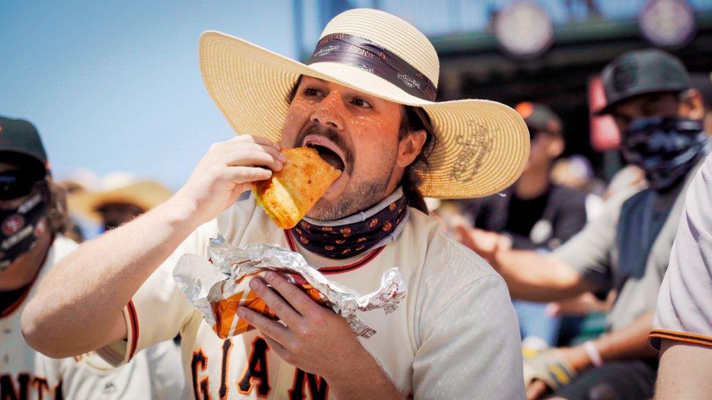 a man in a Giants jersey eats a huge taco