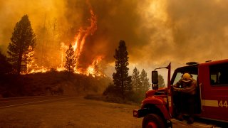 Photo of a firefighter heading toward a wildfire