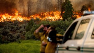 U.S. Forest Service firefighters Chris Voelker, left, and Kyle Jacobson monitor the Sugar Fire