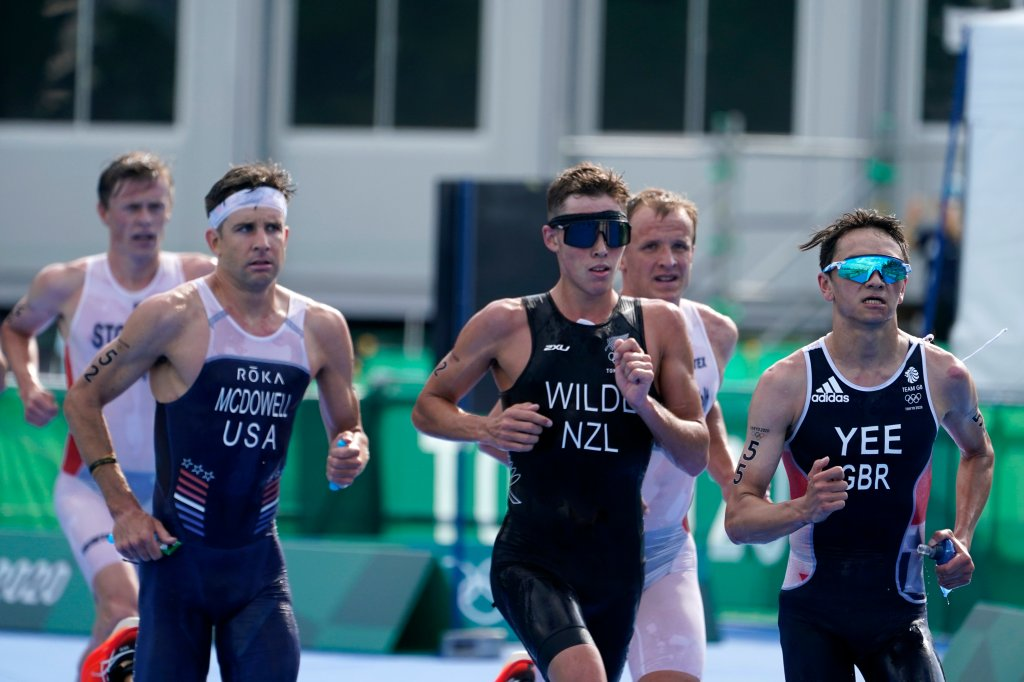 Alex Yee of Great Britain leads a group including Hayden Wilde of New Zealand, center, and Kevin McDowell of United States, left, during the run portion of the men's individual triathlon at the 2020 Olympics on July 26, 2021, in Tokyo, Japan.