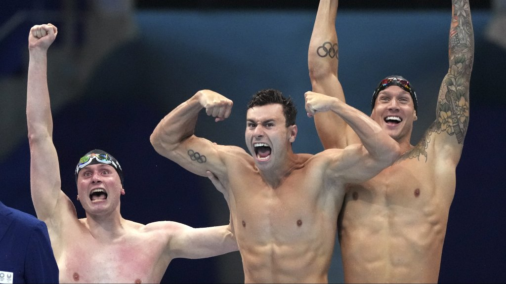 United States men's 4x100m freestyle relay team Bowen Beck, Blake Pieroni, and Caeleb Dressel celebrate after winning the gold medal at the 2020 Summer Olympics, Monday, July 26, 2021, in Tokyo, Japan.