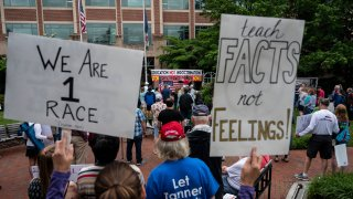"""People hold up signs during a rally against """"critical race theory"""" (CRT) being taught in schools at the Loudoun County Government center in Leesburg, Virginia on June 12, 2021."""