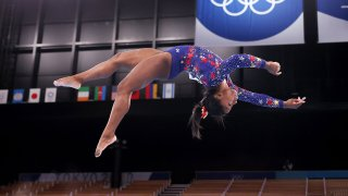 Simone Biles does a layout on the balance beam during women's gymnastics qualifications