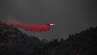 A plane releases fire retardant on a ridge while battling the Salt Fire.