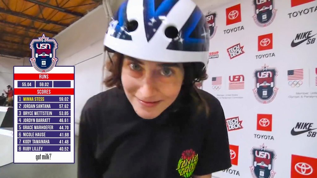 a skateboarder who just finished a winning run makes a silly face at the camera while still wearing her helmet
