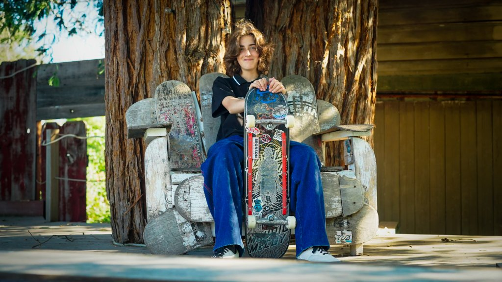 A teenage girl sits with a skateboard on a chair made of skateboards under a tree
