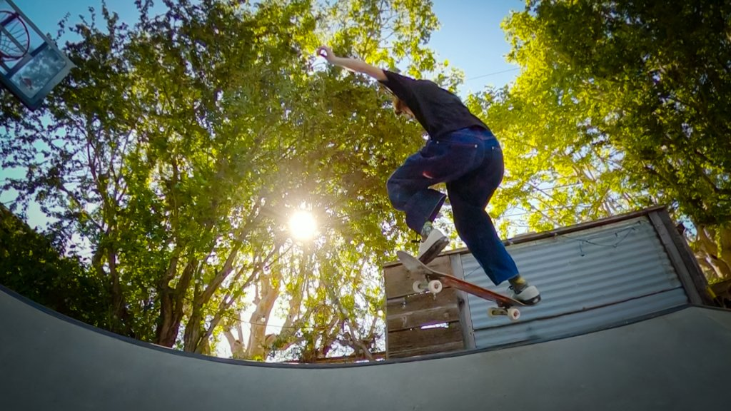 skateboarder jumps in the air with trees and a setting sun behind her