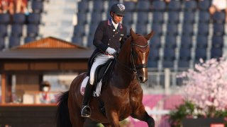 Steffen Peters rides Mopsie, a light brown horse, in a dressage arena
