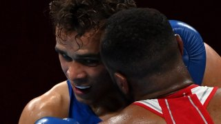Morocco's Youness Baalla (red) and New Zealand's David Nyika fight during their men's heavy (81-91kg) preliminaries round of 16 boxing match during the Tokyo 2020 Olympic Games at the Kokugikan Arena in Tokyo on July 27, 2021.