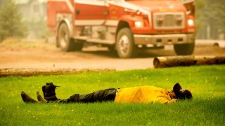 Healdsburg firefighter Justin Potter rests as his crew prepares to battle the Dixie Fire in the Clear Creek community of Lassen County, Calif., on Friday, Aug. 6, 2021.