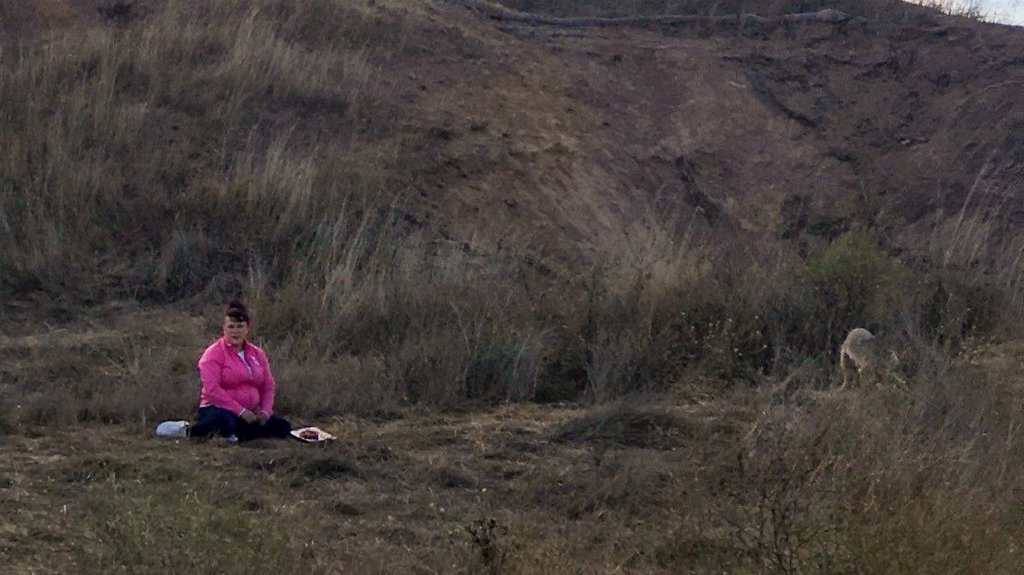A woman with a platter of meat sits on the ground on Bernal Hill in San Francisco, Calif.