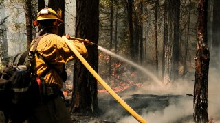 A firefighter works to extinguish a control burn in Greenville, California.