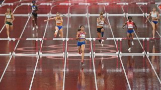 Sydney McLaughlin, centre, of USA on the way to winning the semi-final of the women's 400 metres Hurdles at the Olympic Stadium on day ten of the 2020 Tokyo Summer Olympic Games