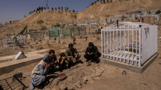 the Ahmadi family pray at the cemetery next to family graves of family members killed by a US drone strike, in Kabul, Afghanistan