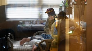 FILE - In this Aug. 18, 2021, file photo, medical staff tend to a patient with coronavirus, on a COVID-19 ward inside the Willis-Knighton Medical Center in Shreveport, La. COVID-19 deaths and cases in the U.S. have climbed back to where they were over the winter, wiping out months of progress and potentially bolstering President Joe Biden's case for sweeping new vaccination requirements.