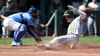 Mark Canha #20 of the Oakland Athletics slides safely into home plate.