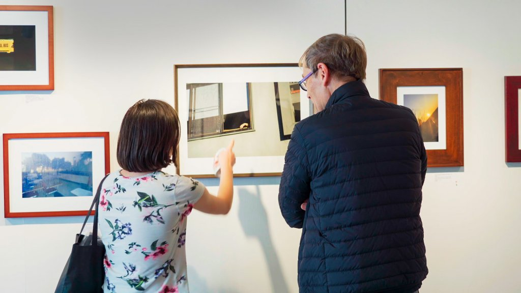 two people look at a photograph in a gallery that depicts a hand resting on the window sill of a house or apartment.