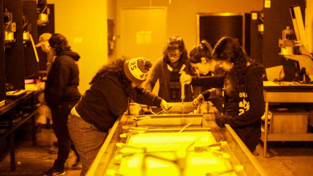 students crowd around a darkroom sink under orange light