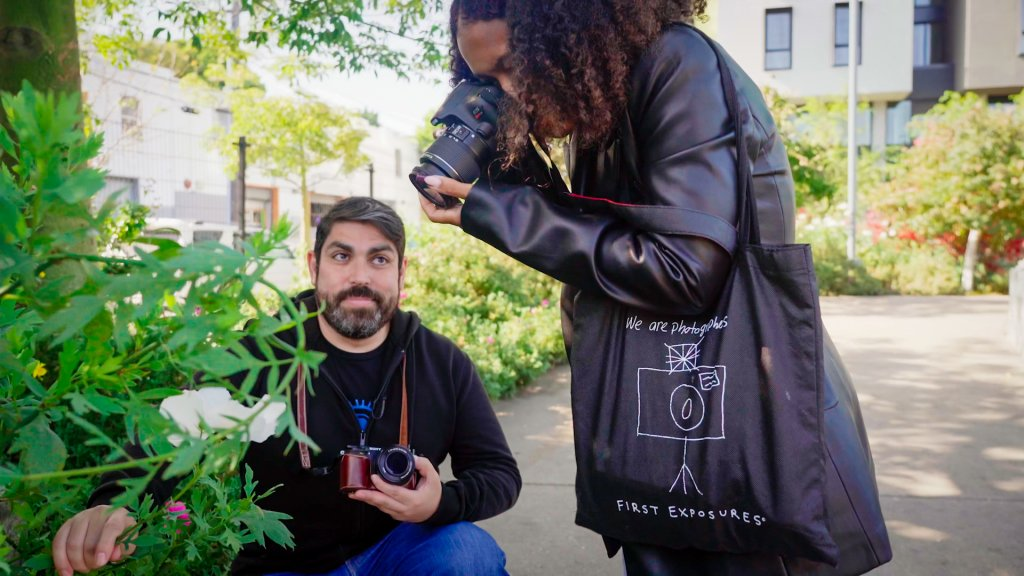 teen girl photographs a flower as a bearded man holds it still for her