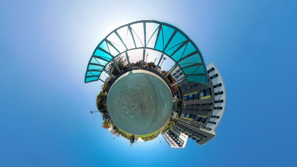 tiny planet photo of an outdoor gazebo with a mid-rise building next to it