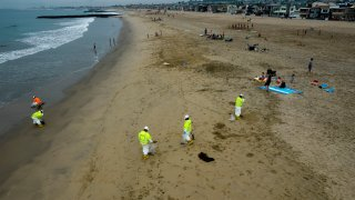 Workers in protective suits clean the contaminated beach