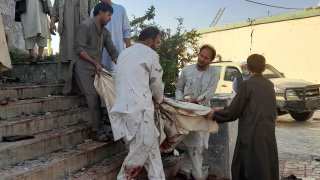 People carry the body of a victim from a mosque following a bombing in Kunduz province