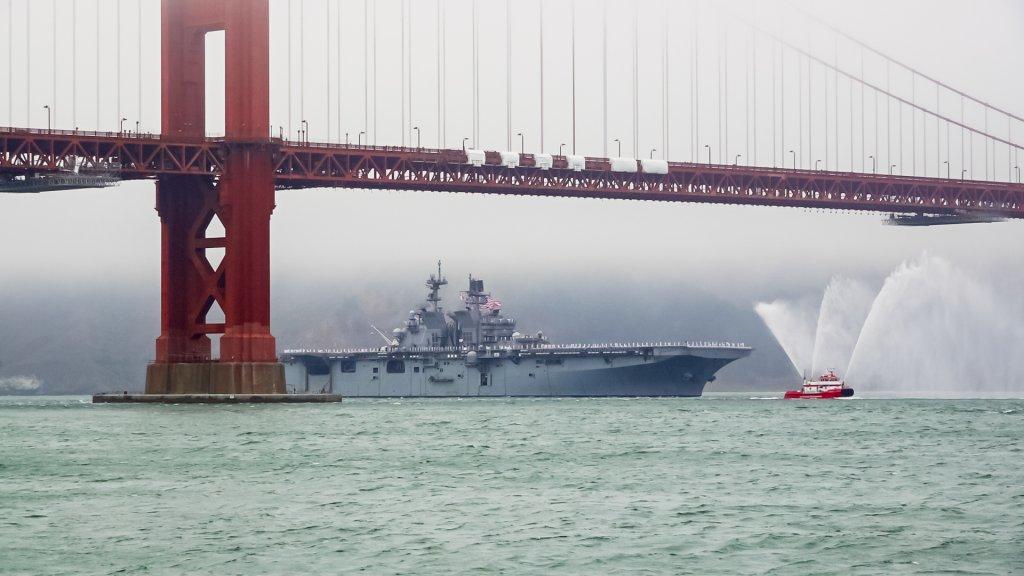 Large Navy ship sails under the Golden Gate Bridge