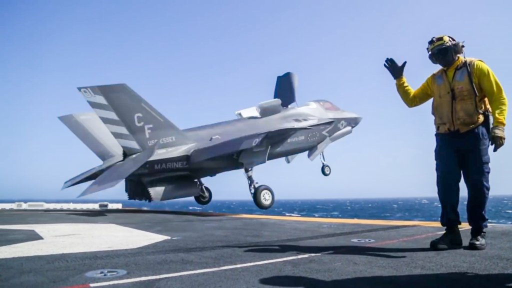 A fighter jet launches from the deck of a Navy ship.