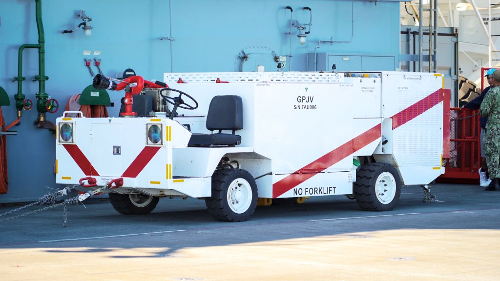 An onboard firefighting truck parked on the flight deck of a ship